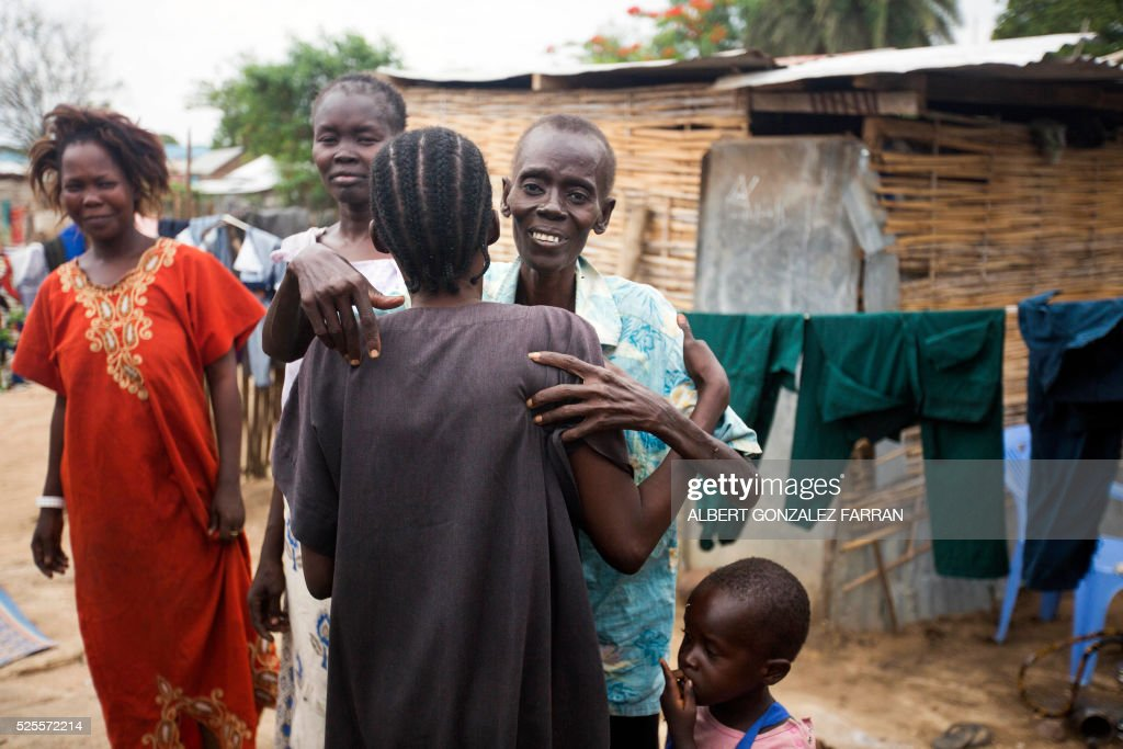 Esther Abraham, a terminally ill HIV positive woman, greets her sister outside her shelter in Juba on April 28, 2016. South Sudan experiences a generalised HIV epidemic, with concentration of high prevalence in urban areas, basically in the Equatorial region. According to UN AIDS, nearly 3% of the adult population is HIV positive, with 13,000 deaths every year and 18,000 new infections annually. However, these figures should be likely higher if there was a more accurate evaluation among the rural population. / AFP / Albert Gonzalez Farran