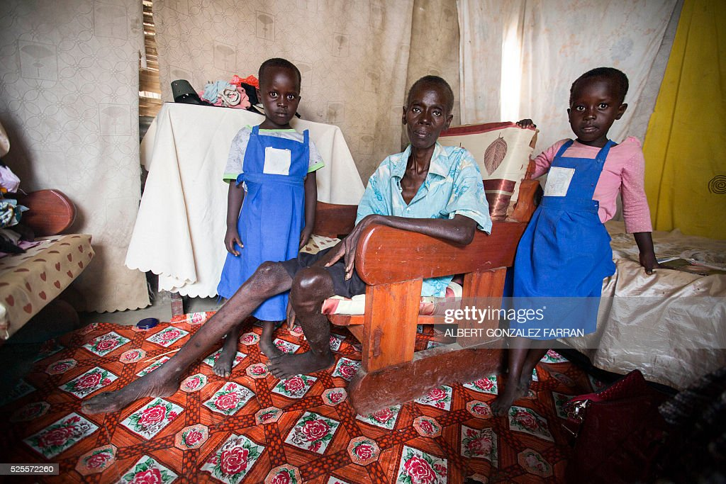 Esther Abraham (C), a terminally ill HIV positive woman, poses with her two nieces in their shelter in Juba on April 28, 2016. South Sudan experiences a generalised HIV epidemic, with concentration of high prevalence in urban areas, basically in the Equatorial region. According to UN AIDS, nearly 3% of the adult population is HIV positive, with 13,000 deaths every year and 18,000 new infections annually. However, these figures should be likely higher if there was a more accurate evaluation among the rural population. / AFP / Albert Gonzalez Farran