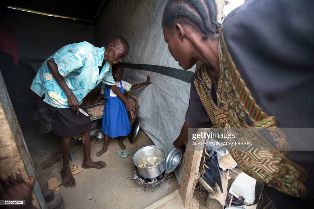 Esther Abraham (L), a terminally ill HIV positive woman, prepares the lunch with her sister in their shelter in Juba on April 28, 2016. South Sudan experiences a generalised HIV epidemic, with concentration of high prevalence in urban areas, basically in the Equatorial region. According to UN AIDS, nearly 3% of the adult population is HIV positive, with 13,000 deaths every year and 18,000 new infections annually. However, these figures should be likely higher if there was a more accurate evaluation among the rural population. / AFP / Albert Gonzalez Farran
