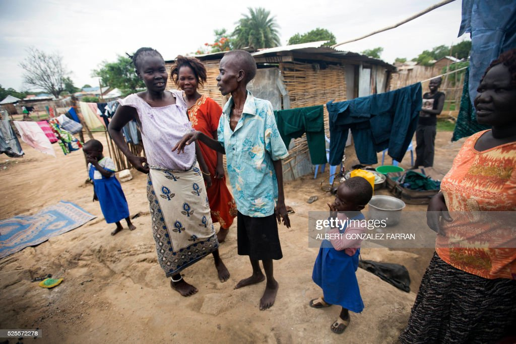 Esther Abraham (C), a terminally ill HIV positive woman, walks outside her shelter surrounded by her relatives and neighbours in Juba on April 28, 2016. South Sudan experiences a generalised HIV epidemic, with concentration of high prevalence in urban areas, basically in the Equatorial region. According to UN AIDS, nearly 3% of the adult population is HIV positive, with 13,000 deaths every year and 18,000 new infections annually. However, these figures should be likely higher if there was a more accurate evaluation among the rural population. / AFP / Albert Gonzalez Farran