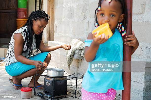 Esther Henry John prepares tea with environmentally friendly charcoal at her home in Dar es Salaam Tanzania on March 10 2015 Looking on is her...