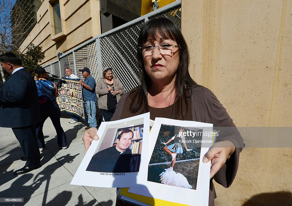 Esther Millar, 54, holds up picture of herself in cheerleading uniform and a picture of father Michael Nocita, the priest who allegedly abused her, during a news conference by victims of sexual abuse by priests in the Catholic Archdiocese of Los Angeles, to urge abused victims to come forward on February 1, 2013 at Cathedral of Our Lady of the Angels in Los Angeles, California. Retired Cardinal Roger Mahony of Catholic Archdiocese of Los Angeles, who avoided criminal charges over the way he handled pedophile priests during his career, was reportedly stripped of his archdiocese duties February 1, by his successor Archbishop Jose Gomez.