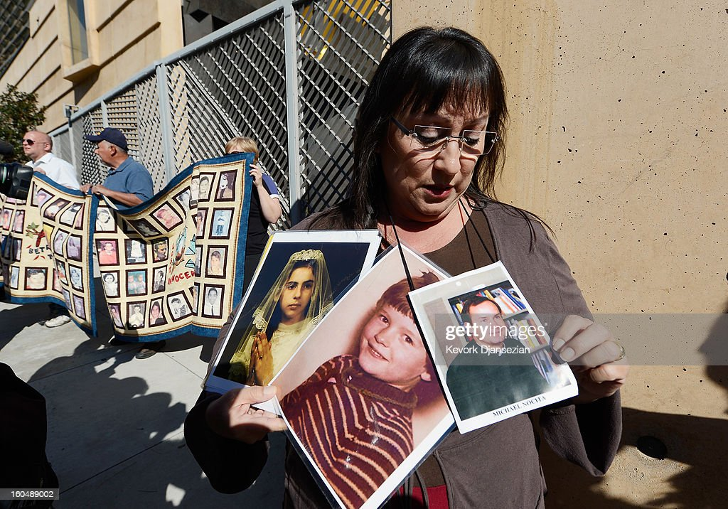 Esther Millar, 54, holds up pictures of Vicki and Mary, who she says were victims of sexual abuse by a priest in the Catholic Archdiocese of Los Angeles, and a picture of father Michael Nocita, the priest who allegedly abused her, during a news conference urging those with information about alleged abuse to come forward on February 1, 2013 at Cathedral of Our Lady of the Angels in Los Angeles, California. Retired Cardinal Roger Mahony of Catholic Archdiocese of Los Angeles, who avoided criminal charges over the way he handled pedophile priests during his career, was reportedly stripped of his archdiocese duties February 1, by his successor Archbishop Jose Gomez.