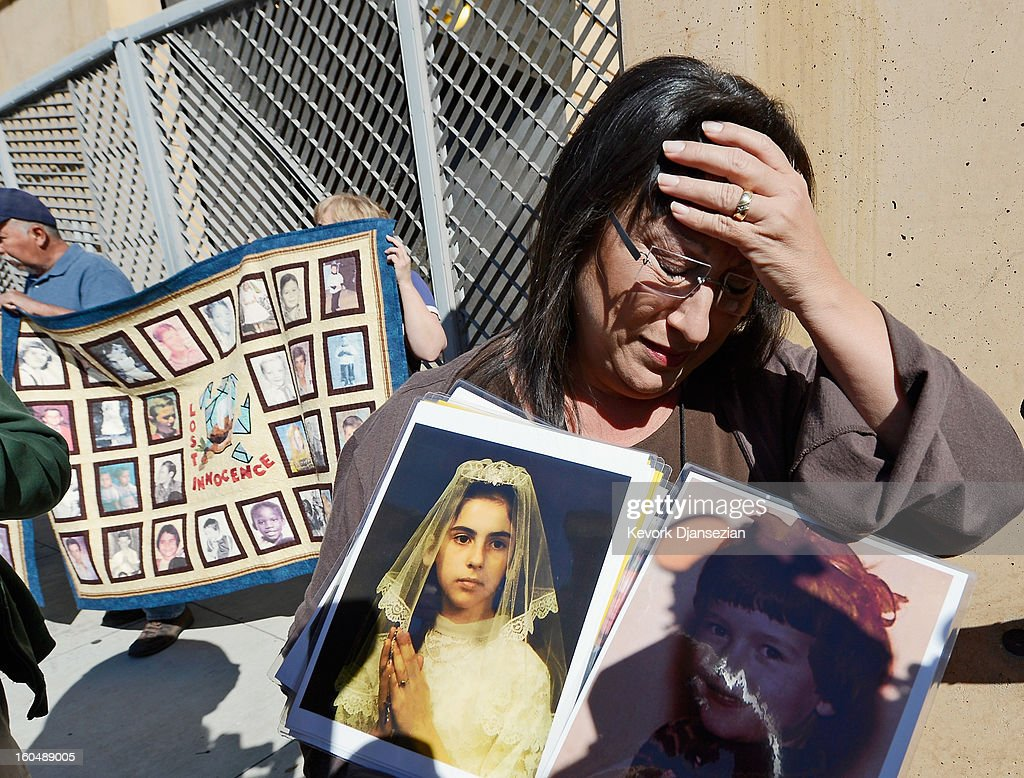 Esther Millar, 54, is overcome with emotion as she talks about her abuser, while holding pictures of Vicki and Mary, who she says were victims of sexual abuse by priest in the Catholic Archdiocese of Los Angeles, during a news conference urging those with information about alleged abuse to come forward on February 1, 2013 at Cathedral of Our Lady of the Angels in Los Angeles, California. Retired Cardinal Roger Mahony of Catholic Archdiocese of Los Angeles, who avoided criminal charges over the way he handled pedophile priests during his career, was reportedly stripped of his archdiocese duties February 1, by his successor Archbishop Jose Gomez.