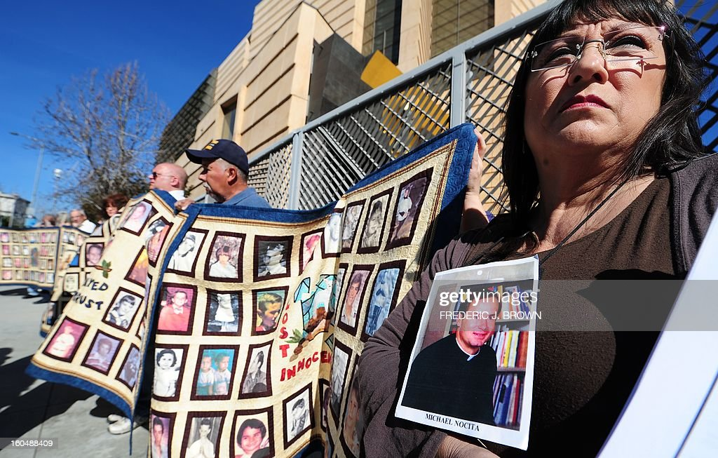 Esther Miller holds a picture and the released documents on Reverand Michael Nocita as victims and their supporters hold quilts bearing portraits of abused children while gathered outside the Cathedral of Our Lady of the Angels in Los Angeles, California, on February 1, 2013, one day after the release of personnel files of priests accused of sexual misconduct. The archbishop of Los Angeles Jose Gomez stripped his predecessor, retired Cardinal Roger Mahony, of all church duties on January 31. In all, 124 files were released on the Los Angeles archdiocese's website, listed by priests' names, including 82 containing information on allegations of childhood sexual abuse.. AFP PHOTO / Frederic J. BROWN