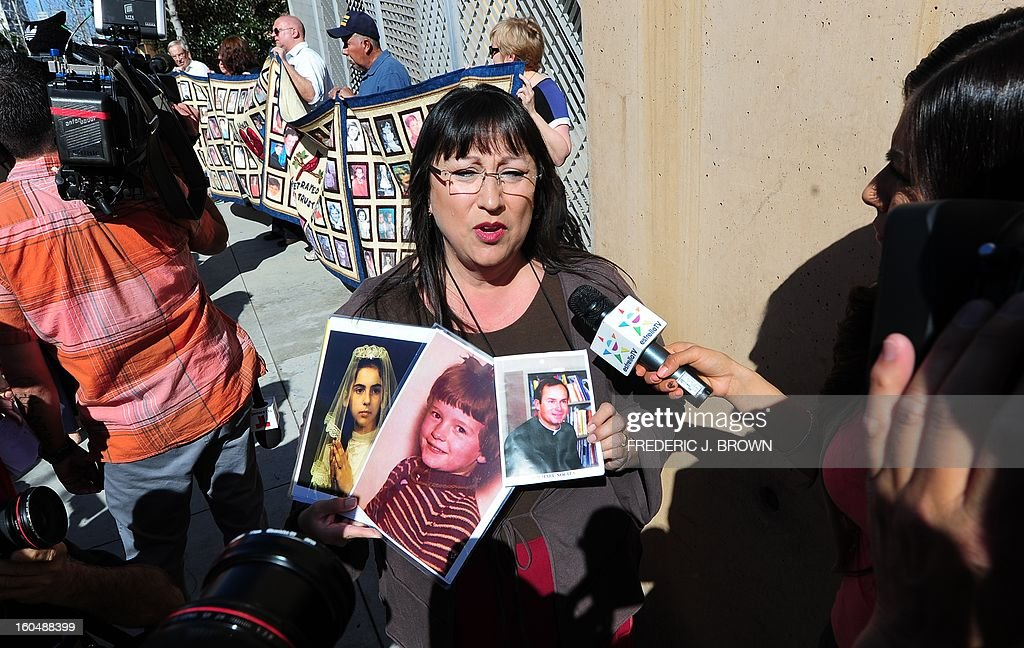 Esther Miller holds pictures of abused children and a priest while addressing the media as victims and their supporters hold quilts bearing portraits of young children outside the Cathedral of Our Lady of the Angels in Los Angeles, California, on February 1, 2013, one day after the release of personnel files of priests accused of sexual misconduct. The archbishop of Los Angeles Jose Gomez stripped his predecessor, retired Cardinal Roger Mahony, of all church duties on January 31. In all, 124 files were released on the Los Angeles archdiocese's website, listed by priests' names, including 82 containing information on allegations of childhood sexual abuse.. AFP PHOTO / Frederic J. BROWN