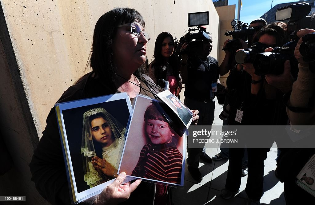 Esther Miller holds pictures of abused children and Reverand Michael Nocita, including his released documents, as abuse victims and their supporters gathered outside the Cathedral of Our Lady of the Angels in Los Angeles, California, on February 1, 2013, one day after the release of personnel files of priests accused of sexual misconduct. The archbishop of Los Angeles Jose Gomez stripped his predecessor, retired Cardinal Roger Mahony, of all church duties on January 31. In all, 124 files were released on the Los Angeles archdiocese's website, listed by priests' names, including 82 containing information on allegations of childhood sexual abuse. AFP PHOTO / Frederic J. BROWN