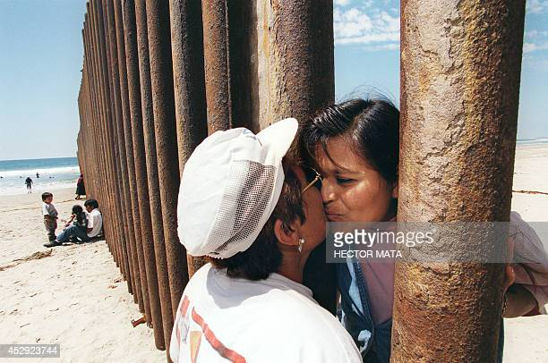 Esther Pereyra Rubalcaba kisses her daughter Patricia through the wall separating the US and the Mexican territories in Tijuana Mexico 19 August 1997...