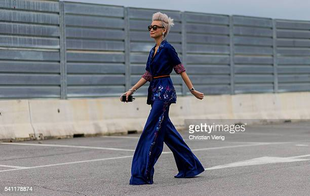 Esther Quek wearing a navy Etro suit outside Versace during the Milan Men's Fashion Week Spring/Summer 2017 on June 18 2016 in Milan Italy
