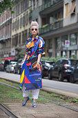 Esther Quek wears white Dolce Gabbana sunglasses and a bold stainedglass style colorful blue Ralph Lauren belted trench and blue Louboutin heels...