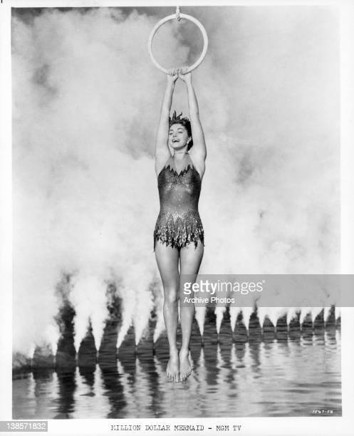 Esther William holding onto a ring and swinging precisionly above smokey water in a scene from the film 'Million Dollar Mermaid' 1952