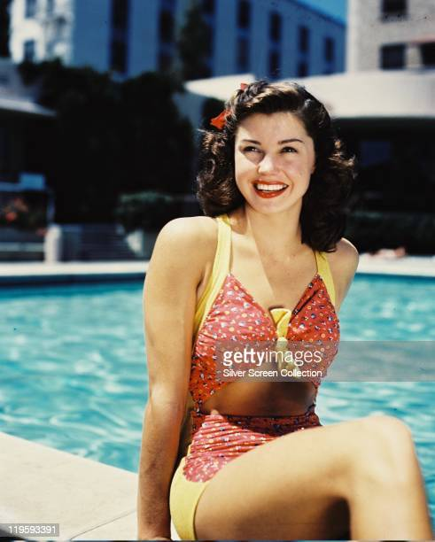 Esther Williams US actress and former Olympic swimmer wearing a redandyellow bathing costume smiling as she poses at the edge of a swmiming pool...