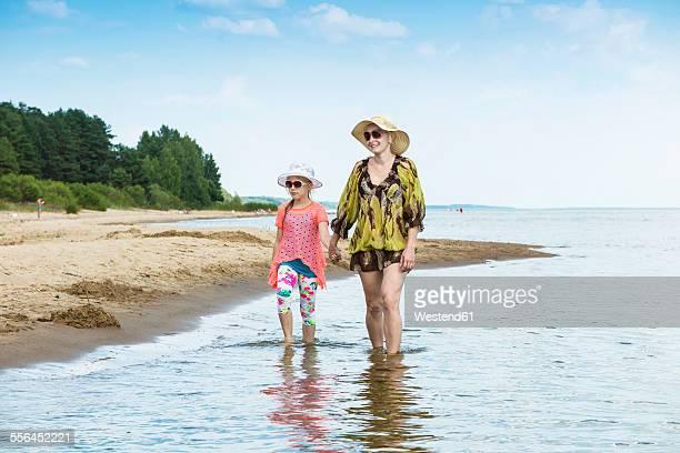 Estonia, Lake Peipus, Kauksi beach, mother and daughter walking in shallow water