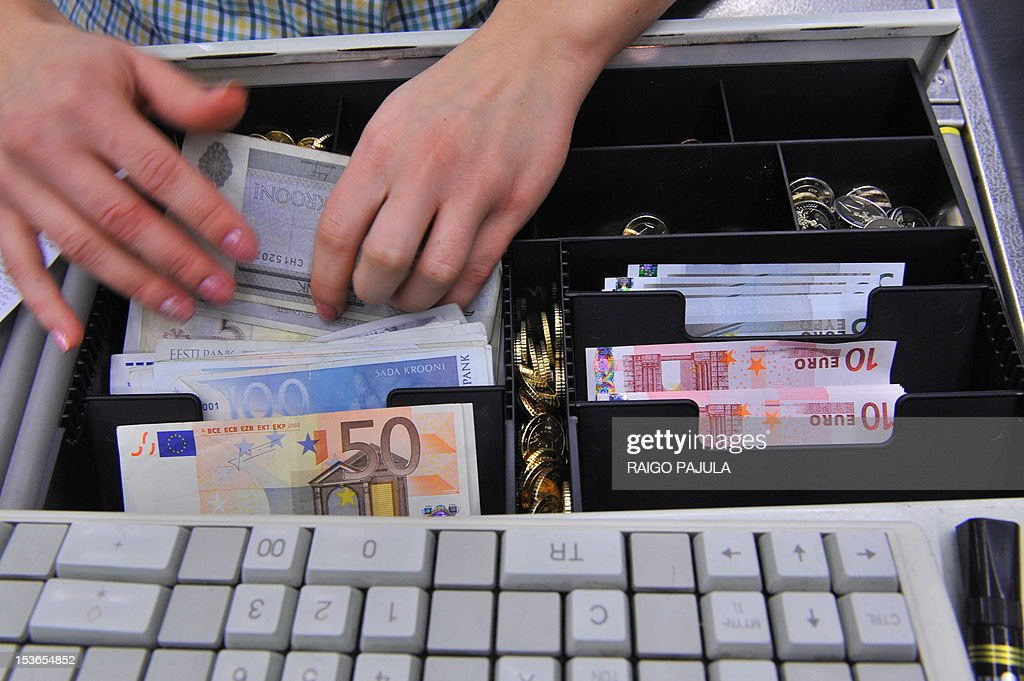 A Estonian cashier puts Estonian crowns and euro notes in a cash desk in a supermarket in Tallinn on January 1, 2011. Estonia adopted the European single currency at midnight, ringing in 2011 as the 17th member of the eurozone, a bloc threatened by bailouts in Greece and Ireland and debt woes in Portugal and Spain. As a spectacular fireworks show lit up the sky over Tallinn, the 2004 Baltic EU entrant of 1.3 million which broke free from the crumbling Soviet Union in 1991 bade a reluctant farewell to its kroon, adopted in 1992 to replace the Soviet ruble. While the centre-right government of Prime Minister Andrus Ansip has championed the switch to the euro as economic good sense despite the eurozone's turmoil, replacing Estonia's highly symbolic kroon has received a muted welcome among average Estonians. = ESTONIA OUT =