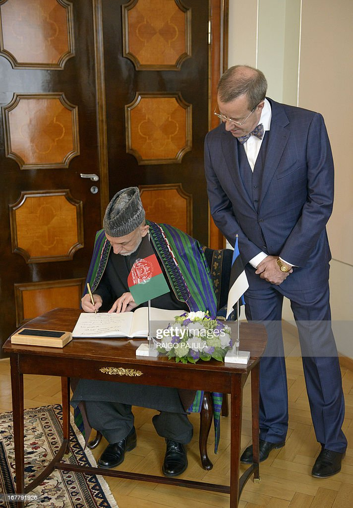 Estonian President Toomas Hendrik Ilves (R) watches as Afghanistan's President Hamid Karzai (L) signs the guest book after a meeting in Tallinn, Estonia on April 30, 2013. Karzai arrived on Monday, April 29, 2013 for a two day official visit to the Baltic state. AFP PHOTO / RAIGO PAJULA