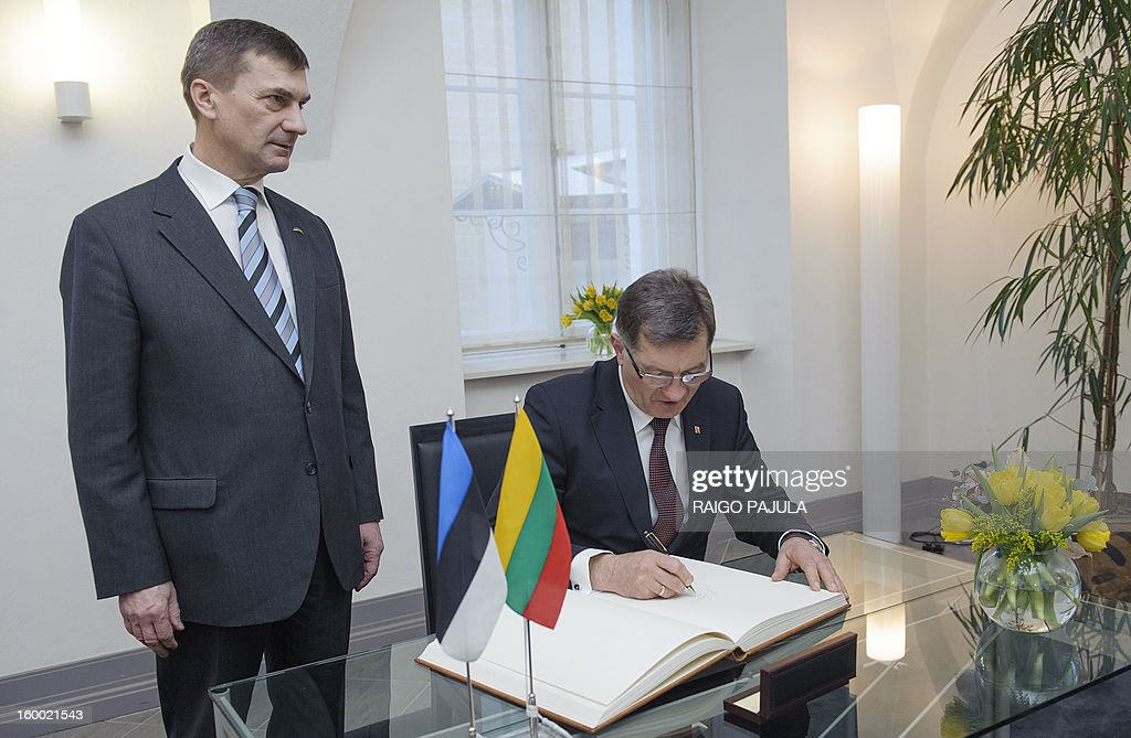 Estonian Prime Minister Andrus Ansip (L) stands next to Lithuanian counterpart Algirdas Butkevicius as he signs a guest book before a joint press conference in Tallinn on January 24, 2013.