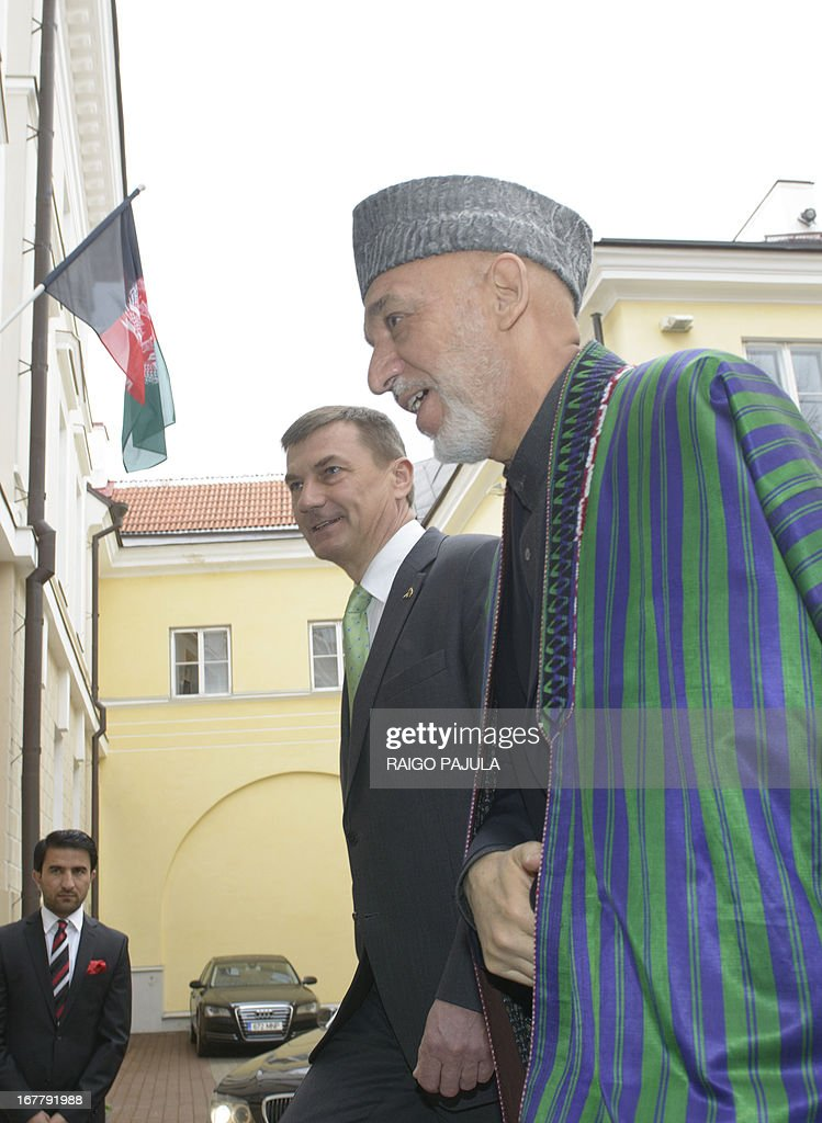 Estonian Prime Minister Andrus Ansip (C) welcomes Afghanistan's President Hamid Karzai (R) arrive for a joint meeting in Tallinn, Estonia on April 30, 2013. Karzai arrived on Monday, April 29, 2013 for a two day official visit to the Baltic state.