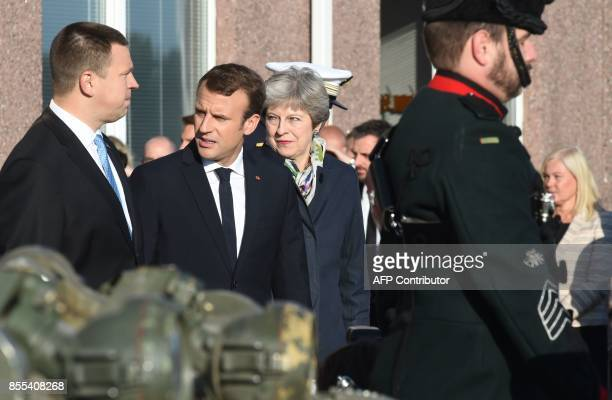 Estonian Prime Minister Juri Ratas French President Emmanuel Macron and British Prime Minister Theresa May arrive to inspect troops at an Estonian...