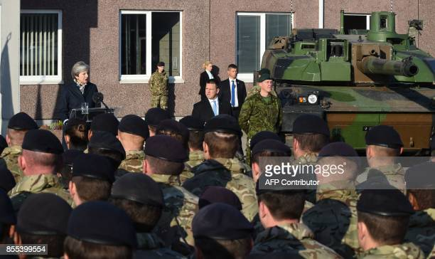 Estonian Prime Minister Juri Ratas listens as British Prime Minister Theresa May talks to soldiers during a visit at an Estonian military base in...