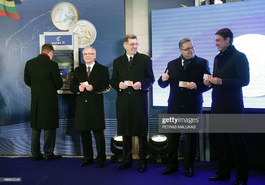 Estonian Prime Minister Taavi Roivas, Lithuania Finance Minister Rimantas Sadzus , Lithuanian Prime Minister Algirdas Butkevicius, and Chairman of the Board of the Bank of Lithuania Vitas Vasiliauskas hold euro notes after Butkevicius symbolically withdrew a 10 euro note from a bank machine on January 1, 2015 during a ceremony in Vilnius. Lithuania switched over to the euro on January 1st, becoming the last Baltic nation to adopt Europe's single currency in a bid to boost stability despite fears of inflation and eurozone debt woes. AFP PHOTO / PETRAS MALUKAS
