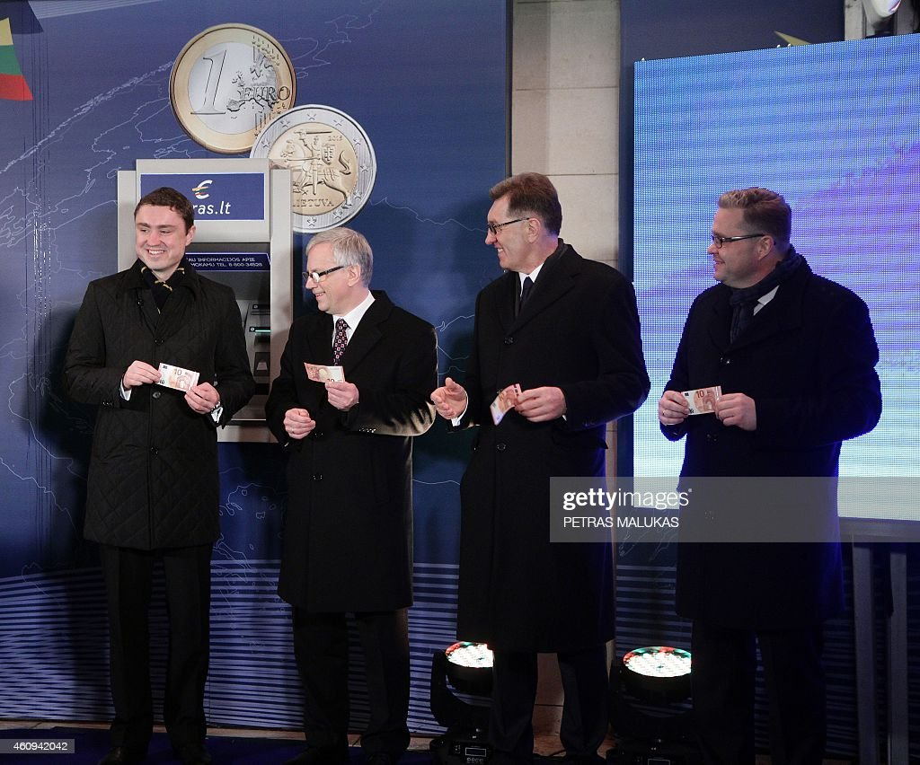 Estonian Prime Minister Taavi Roivas (L), Lithuanian Finance Minister Rimantas Sadzus, Lithuanian Prime Minister Algirdas Butkevicius, Chairman of the Board of the Bank of Lithuania Vitas Vasiliauskas hold euro notes after Butkevicius symbolically withdrew a 10 euro note from a bank machine on January 1, 2015 during a ceremony in Vilnius. Lithuania switched over to the euro on January 1st, becoming the last Baltic nation to adopt Europe's single currency in a bid to boost stability despite fears of inflation and eurozone debt woes. AFP PHOTO / PETRAS MALUKAS