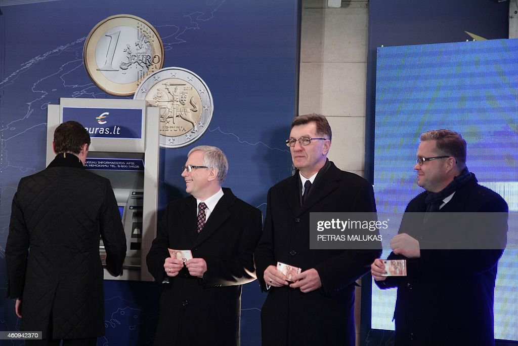 Estonian Prime Minister Taavi Roivas (L), Lithuanian Finance Minister Rimantas Sadzus, Lithuanian Prime Minister Algirdas Butkevicius, and Chairman of the Board of the Bank of Lithuania Vitas Vasiliauskas withdraw euros from a bank machine during a ceremony in Vilnius, on January 1, 2015. Lithuania switched over to the euro on January 1st, becoming the last Baltic nation to adopt Europe's single currency in a bid to boost stability despite fears of inflation and eurozone debt woes. AFP PHOTO / PETRAS MALUKAS
