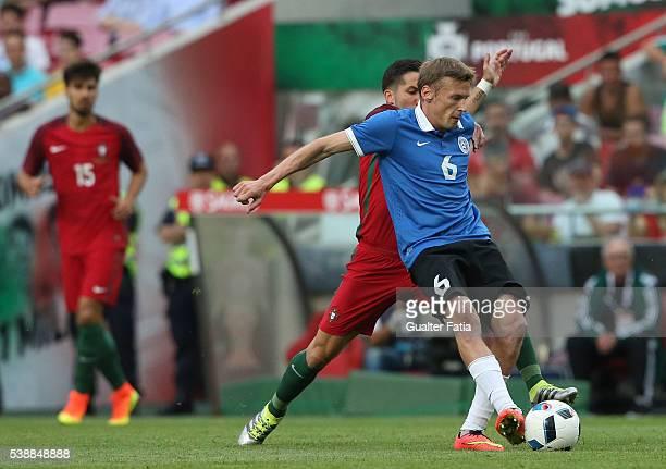 Estonia's midfielder Aleksandr Dmitrijev with Portugal midfielder Joao Moutinho in action during the International Friendly match between Portugal...