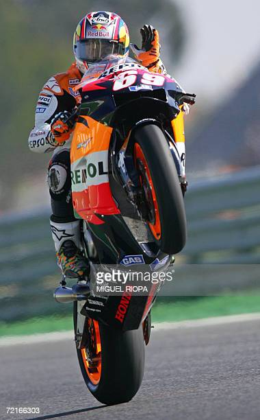 Nicky Hayden from US makes a wheelie as he salutes to supporters after the free practice 3 for the Moto GP World Championship in Estoril 14 October...