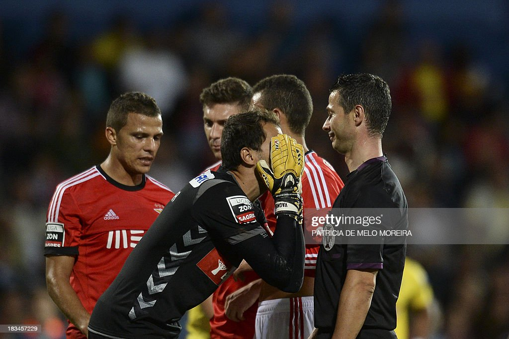 Estoril's Brazilian goalkeeper Vagner Silva (2nd L) argues with referee Manuel Mota (R) after he awarded a penalty during the Portuguese league football match GD Estoril Praia vs SL Benfica at the Antonio Coimbra da Mota stadium in Estoril, outskirts of Lisbon, on October 6, 2013.