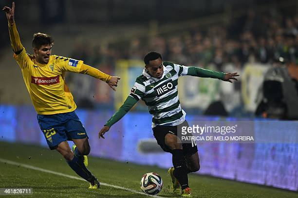 Estoril's midfielder Diogo Amado vies with Sporting's Peruvian forward Andre Carrilho during the Portuguese league football match Estoril Praia vs...