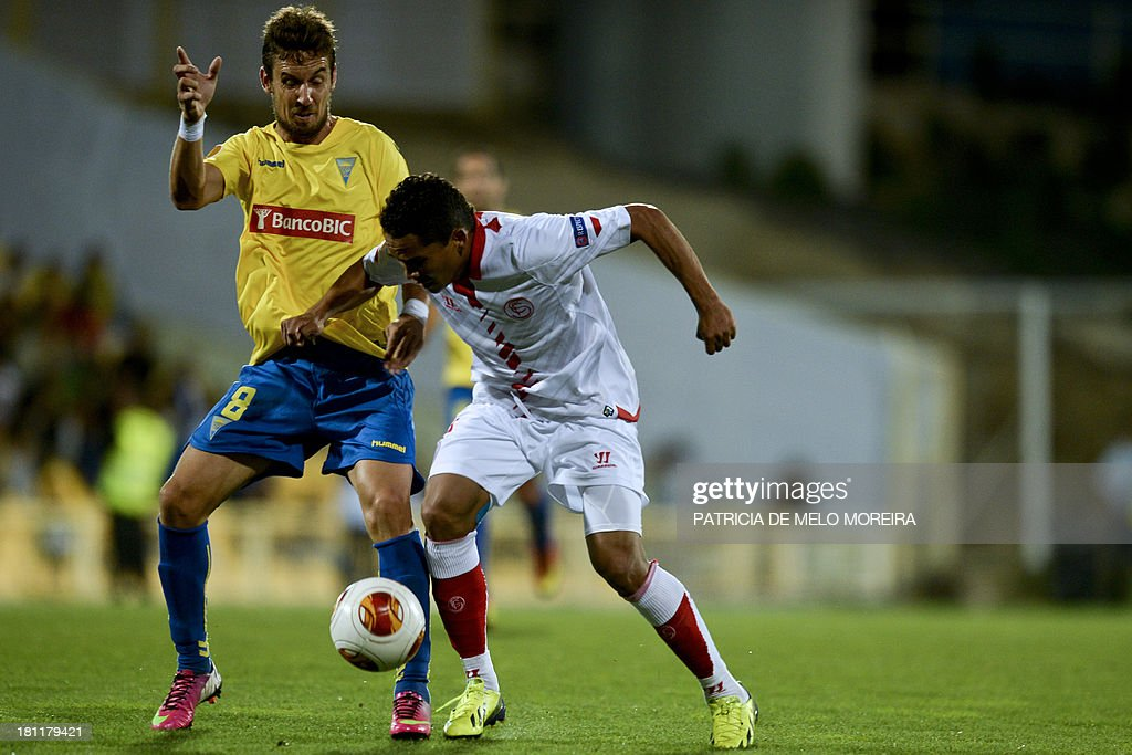Estoril's midfielder Filipe Goncalves (L) vies with Sevilla's Colombian forward Carlos Bacca (R) during the UEFA Europa League, group H, football match Estoril vs Sevilla at the Antonio Coimbra da Mota stadium in Estoril on September 19, 2013.