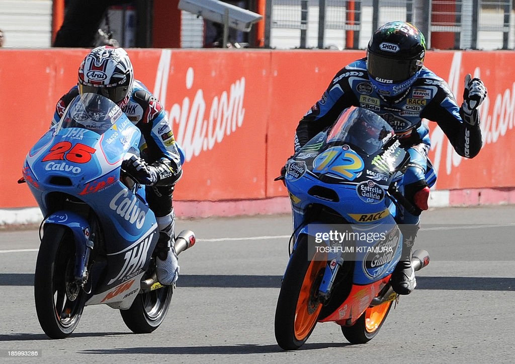 Estrella Galicia rider Alex Marquez of Spain (R) clinches his fist beside Team Calvo rider Maverick Vinales of Spain (L) after crossing the finish line to win the Moto3 race of the Japanese Grand Prix at the Twin Ring Motegi circuit in Motegi on October 27, 2013.
