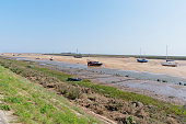From the top of a grass bank, looking out over boats beached on sandbanks to the flat marshes at Wells-next-the-Sea