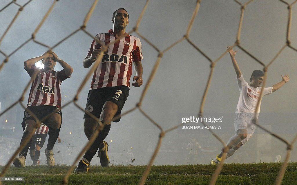 Estudiantes de la Plata defender Leandro Desabato (C) and defender Christian Cellay (L) reacts while Internacional forward Edu celebrates temmate midfielder Giuliano's (out of frame) goal during their Copa Libertadores 2010 quarterfinals footbal match at Quilmes stadium in Buenos Aires, Argentina, on May 20, 2010. Estudiantes won 2-1 but Internacional quailified for next round. AFP PHOTO / Juan Mabromata