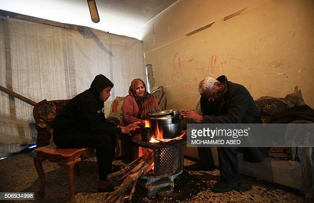 TOPSHOT Etadal Abu Oda a 57yearold Palestinian woman prepares food with her son and her husband Ahmed at their damaged house on January 26 during a...
