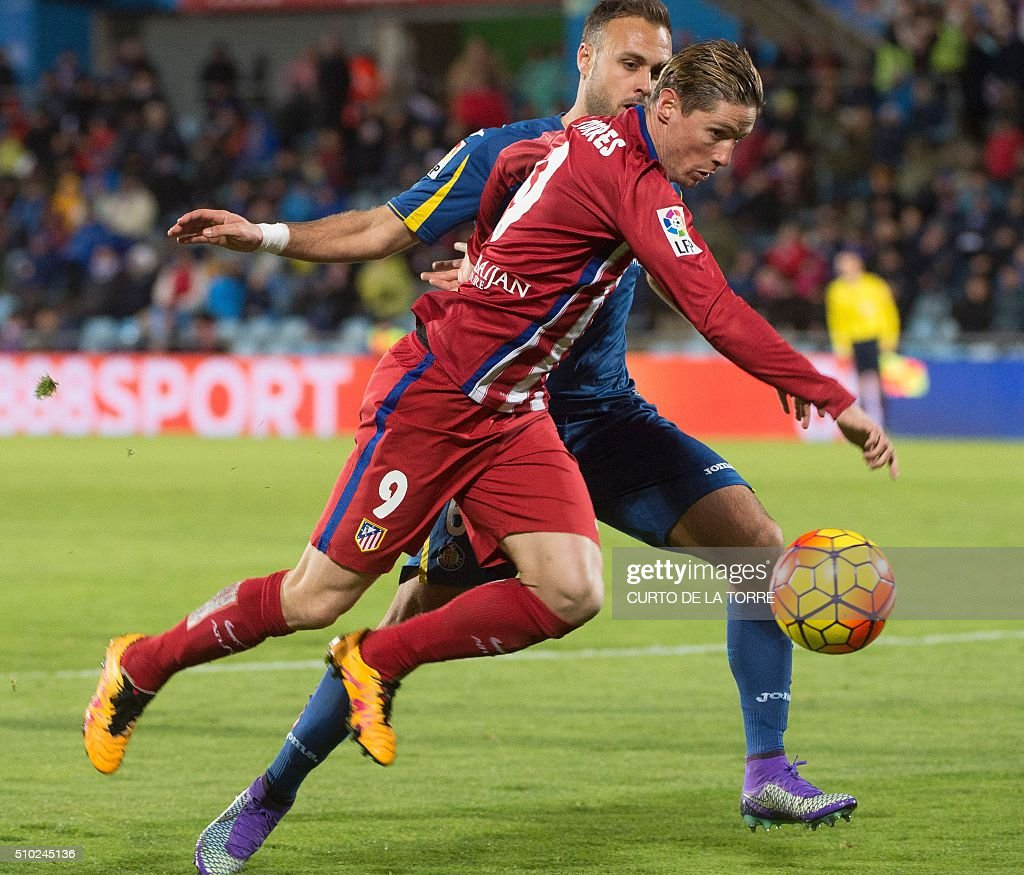 etafe's defender Juan Cala (L) vies with Atletico Madrid's forward Fernando Torres during the Spanish league football match Getafe CF vs Club Atletico de Madrid at the Col. Alfonso Perez stadium in Getafe on February 14, 2016. TORRE