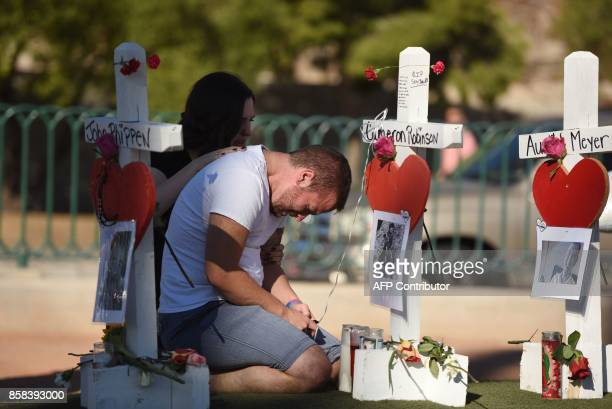 TOPSHOT Ethan Avanzino grieves beside a white cross for his friend Cameron Robinson one of 58 victims of Sunday night's mass shooting on the Las...