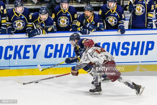 Ethan Holdaway of Trinity College and Todd Jackson of Norwich University battle for the puck during the Division lll Men's Ice Hockey Championship...