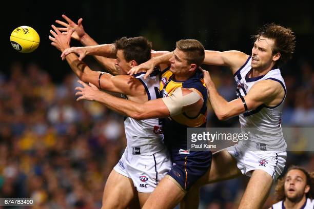 Ethan Hughes and Joel Hamling of the Dockers contest a mark against Nathan Vardy of the Eagles during the round six AFL match between the West Coast...