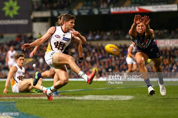 Ethan Hughes of the Dockers attempts to smother the kick by Luke Breust of the Hawks during the round 18 AFL match between the Fremantle Dockers and...