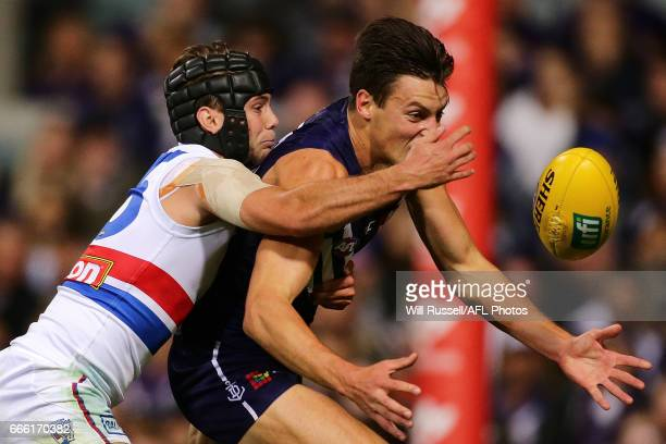 Ethan Hughes of the Dockers is tackled by Caleb Daniel of the Bulldogs during the round three AFL match between the Fremantle Dockers and the Western...
