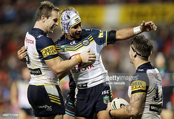 Ethan Lowe of the Cowboys celebrates scoring a try with team mates Johnathan Thurston and Michael Morgan during the round five NRL match between the...