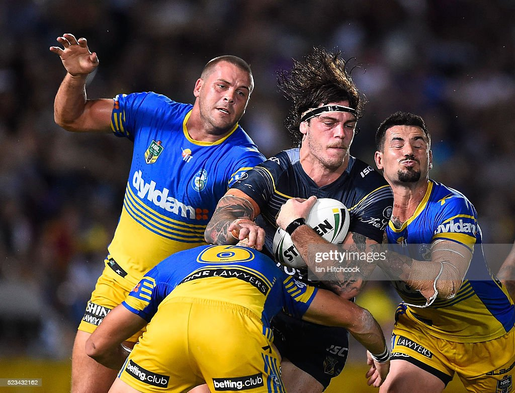 Ethan Lowe of the Cowboys is tackled by Danny Wicks, Corey Norman and Nathan Peats of the Eels during the round eight NRL match between the North Queensland Cowboys and the Parramatta Eels at 1300SMILES Stadium on April 23, 2016 in Townsville, Australia.