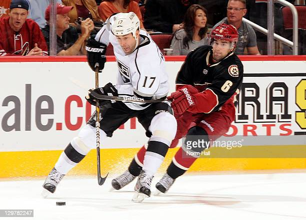 Ethan Moreau of the Los Angeles Kings skates with the puck while fending off David Schlemko of the Phoenix Coyotes at Jobingcom Arena on October 20...