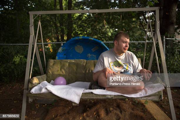 Ethan Poulin rocks in a swing during a weekly visit at his family's home in Manchester Poulin has autism spectrum disorder and intermittent explosive...