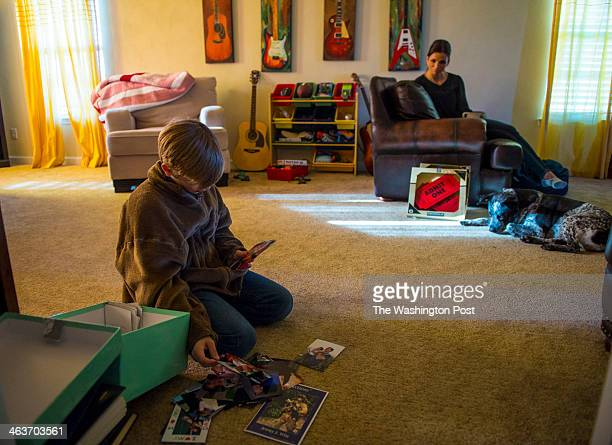 Ethan Prusinski stepson of Jeremy Wise looks through a box of photos of his late stepfather as his mother and widow Dana Bernhardt looks on beside...