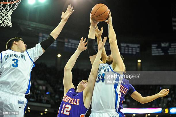 Ethan Wragge and Doug McDermott of the Creighton Bluejays fight with Adam Wing of the Evansville Aces for a rebound during their game at the...