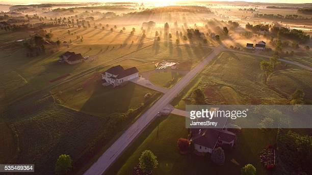 Etherial sunrise through misty fog with long shadows and sunbeams