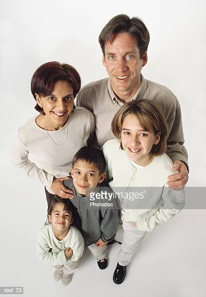 ethically mixed family of five stand together smiling in khaki colored clothes