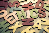 Closeup ETHICS word in scattered wood letters